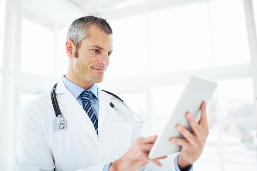 A mature doctor reading a pleasing diagnosis on his touchpad